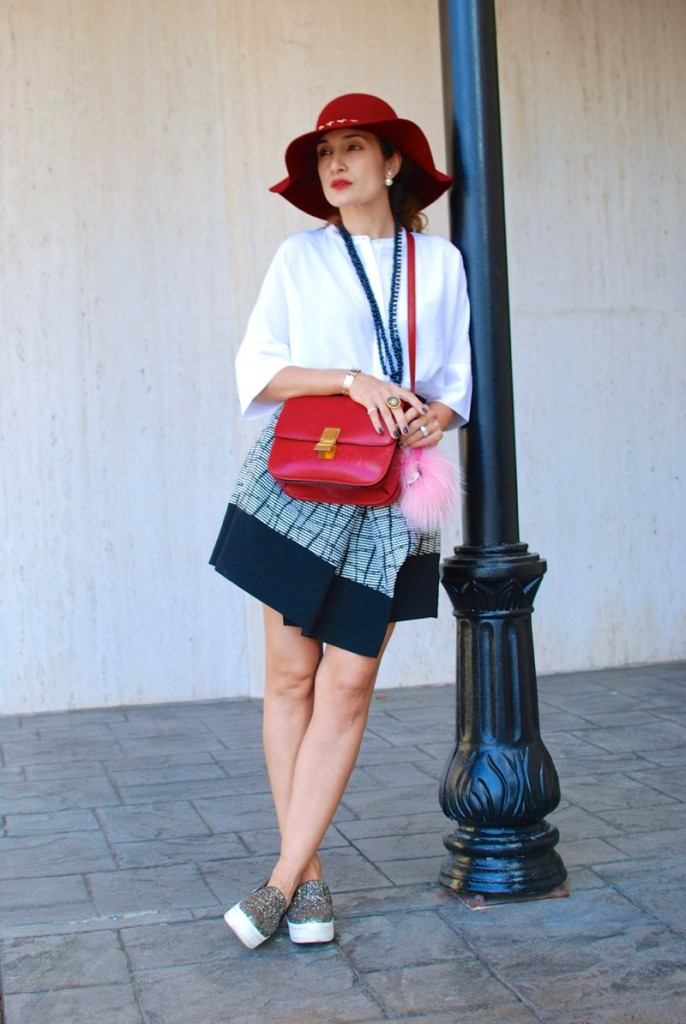 red celine box bag chic balck and white outfit asymmetrical skirt how to style a red bag sparkle sneakers fendi fur charm floppy hat for fall how to wear sneakers casually houston fashion blogger